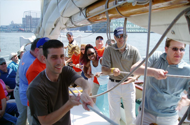 Company Outting doing a teambuilder on Schooner Adirondack III in Boston Harbor raising sail