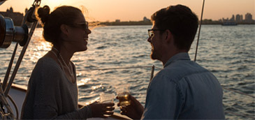 Romantic couple aboard a private yacht during sunset over Boston Harbor